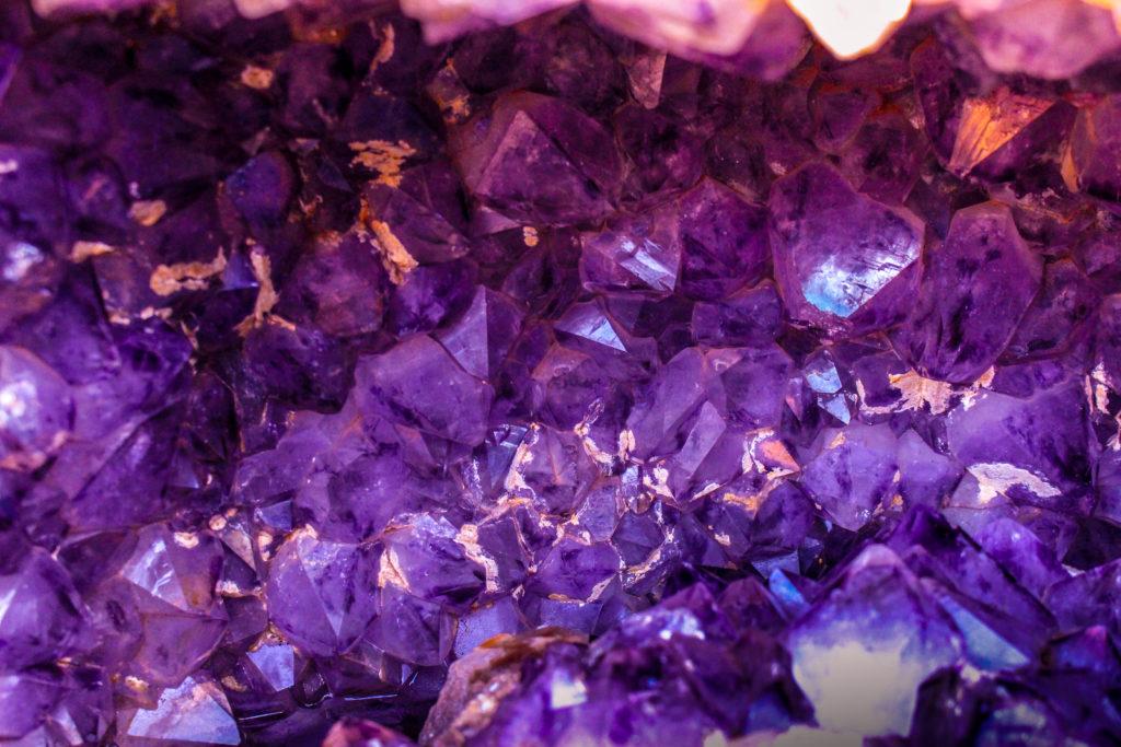 Nahaufnahme einer strahlend violetten Amethyst-Druse. Es sind viele schimmernde Kristallspitzen zu sehen