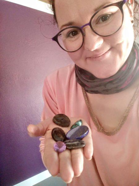 Annika Kayrak, ein Portrait. Sie streckt ihre Hand aus, auf der sie verschiedene Edelsteine hat. Labradorit, Amethyst, Achat, Lapislazuli, Chrysokoll